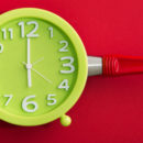 Diet concept with frying pan and green clock on red background. Time for healthy eating. Top view.